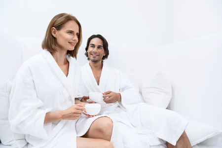 Beautiful woman spending time with smiling man and drinking tea while sitting on white couch in spa center