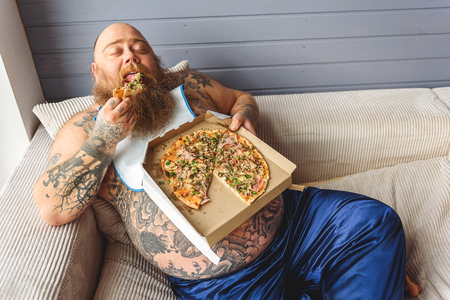 Male heavy eater biting unhealthy food