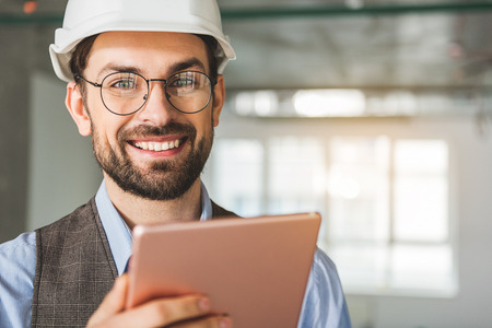 Happy smiling builder keeping tablet