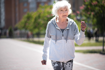 Cheerful aged woman doing sports outdoorsの写真素材