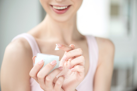 Youthful girl using day cream with joy