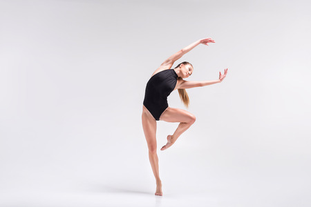Serious young woman performing element of gymnastics choreography