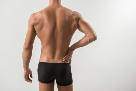 Treat backache. Close-up of back of young sportsman in black underwear. He is touching his loin while suffering from pain. Isolated background