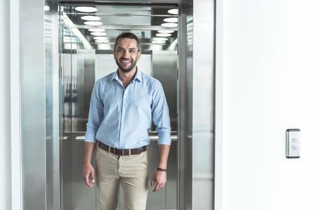Pleasant cute guy is posing against modern lift