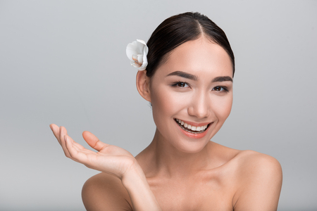 Beauty concept. Portrait of playful young gorgeous asian girl with white orchid in her hair. She is looking at camera with joy while gesticulating positively. Isolated background