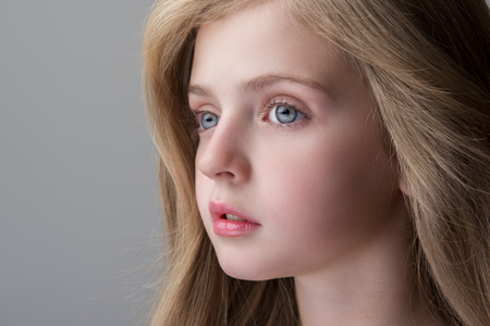 Feeling sadness. Close-up of face of adorable serious little girl is standing and looking aside thoughtfully. Focus on eyes. Isolated background and copy space