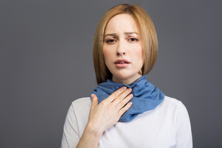Portrait of ill blonde female touching her throat and looking at camera with sadness, her neck wrapped with scarf.