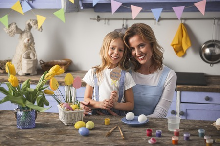 Waist up portrait of content mother and her little kid standing at the kitchen table and looking at camera. Easter decorations and paints are on the desk