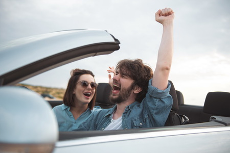 I feel free. Overjoyed young bearded man is driving car while travelling with his gorgeous girlfriend. They are enjoying weekend. Focus on screaming guy is sitting with raised hand and closed eyes