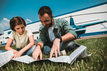 Portrait of calm kid and beaming bearded father looking at map while resting on green field during sunny day