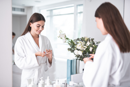 Portrait of happy woman keeping special liquid for taking care of skin on hands, while standing opposite mirror in bathrobe near flowers in white bright apartment