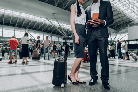 Stay here. Full length portrait of adult man and woman are waiting for their flight, while holding passport with tickets