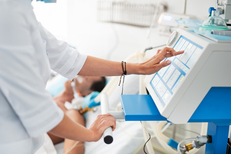 Photo pour Close up of female hands checking medical equipment. Patient on breathing machine lying in bed on blurred background - image libre de droit