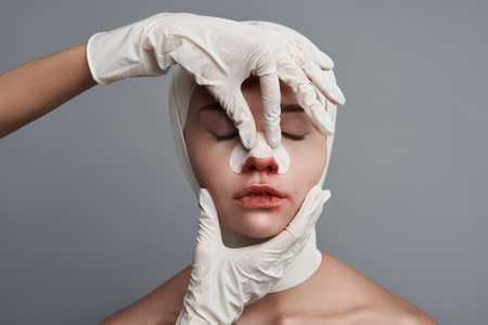 Calm young lady having bandages on her head and sitting with her eyes closed while professional doctor touching her bloody nose