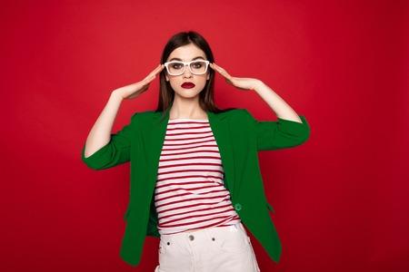 Young stylish lady gracefully holding on glasses