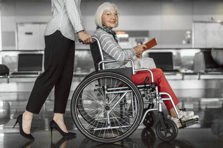Female worker accompanying elderly woman in wheelchair at airport