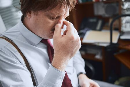 Photo for Middle-aged male office worker rubbing his nose tired of glasses - Royalty Free Image