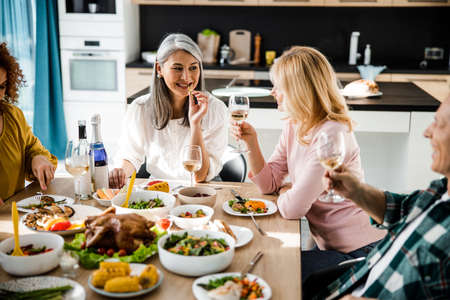 Photo pour Smiling two women looking each other at the festive table in a cozy home - image libre de droit