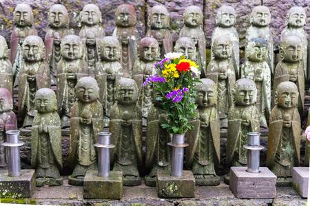 Japanese smile stone buddha monk statue (Jizo Bosatsu), Japanese believe that they can help protect tourists and children to survive, Hasedera Temple, Kamakura, Japan