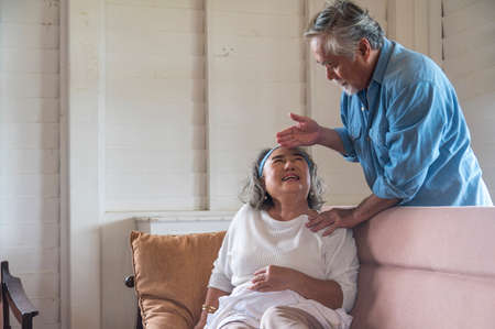 Photo pour Asian senior husband take care and comforting ill wife in living room .- retired elder lover couple lifestyle - image libre de droit