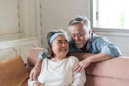 Photo pour Asian senior husband hug relax and smile wife take care in living room .- retired elder lover couple lifestyle - image libre de droit