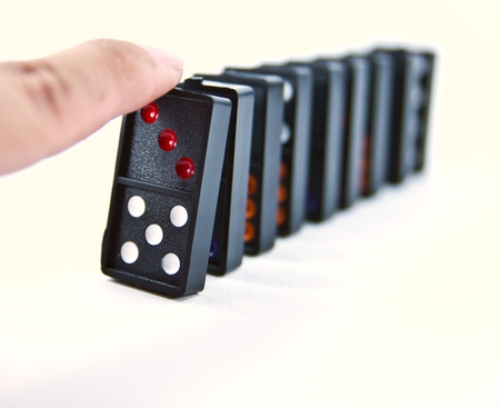A finger ready to start domino chain reaction.
