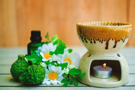 Photo for Aromatherapy essential oil burner on the wooden table with bergamot and flower for spa and relaxation - Royalty Free Image