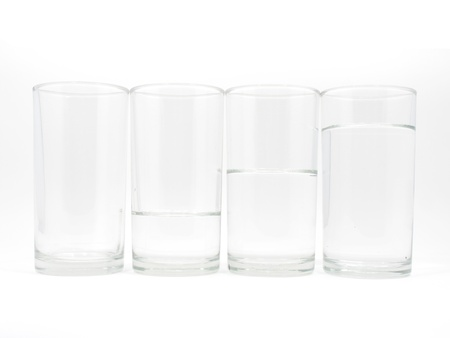 Four glasses with three level of water on white background