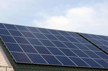 Photo for Renewable clean green energy saving efficient photovoltaic solar panels on a green roof and the cloudless blue sky. - Royalty Free Image