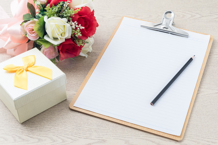 Photo pour Wooden Clipboard attach planning paper with pencil on top beside rose bouquet  ,gift box on table - image libre de droit