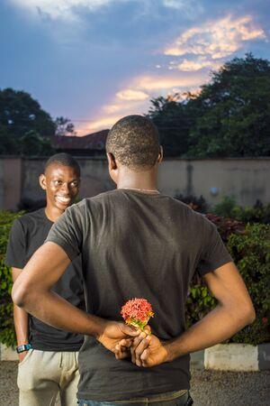 Photo pour young black man holding flowers behind his back waiting to surprise his lover - image libre de droit