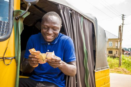 Photo pour young african man driving a rickshaw taxi counting his money smiling - image libre de droit