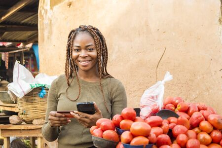 Photo pour young african woman in a local african market using her mobile phone and credit card - image libre de droit