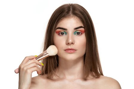Portrait of beautiful young woman with brushes for make-up. Isolated over white background.