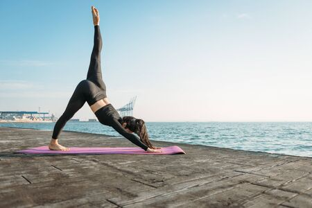 Photo for Young brunette woman in a black jumpsuit practicing yoga on the beach at sunrise. Concept of wellness and healthy lifestyle. - Royalty Free Image