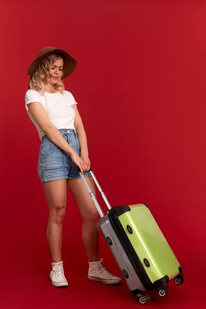 Young blond curly woman in a sundown hat feels upset and tired holding heavy grey luggage bag while standing infront of a red background. Concept of traveling