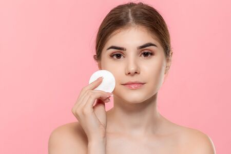 Photo pour Beautiful model applyes cosmetic product to skin with white cotton sponge. Model looks at the camera isolated over pink background. Concept of beauty and health treatment. - image libre de droit