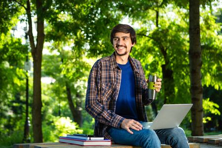 Photo for Young brunet freelancer with beard and mustache sitting with a laptop and coffee in a park. Work at any place - Royalty Free Image