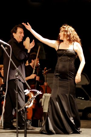 ISTANBUL - JULY 11: Members of the Maltepe Symphonic Orchestra perform live at Maltepe open air stage. Soprano Selva Erdener with conductor Naci Ozguc