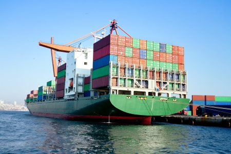 Green cargo ship in port, fully loaded with containers