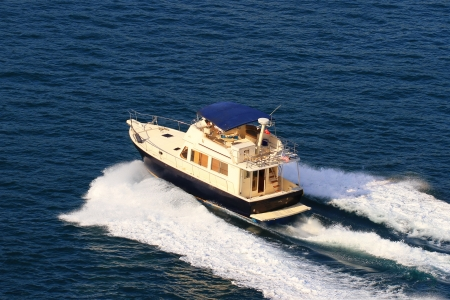 Aerial view of a yacht with splash and wake