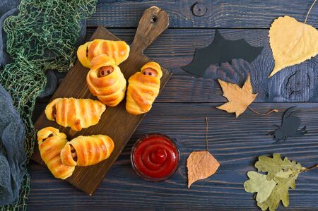 Photo for Funny sausage mummies in dough with ketchup on table. Halloween food. Top view. Flat lay - Royalty Free Image