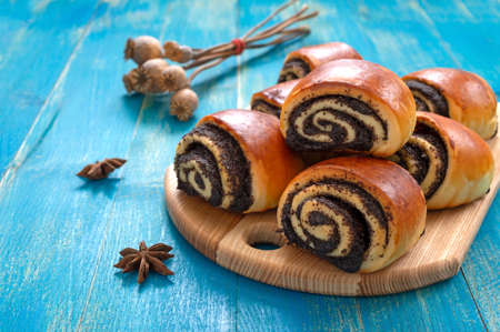Photo for Tasty buns rolls with poppy filling on a blue wooden background. - Royalty Free Image