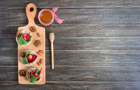 Photo for Tasty and healthy canapes with craft cheese, olives, nuts and whole grain bread on a board. Original party snacks. Copy space - Royalty Free Image