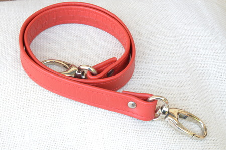 A white bag with red belt