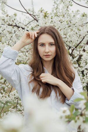 Foto de Girl walk in the flower garden. Young woman in a cherry orchard in spring. Photo of a girl between flowering trees. In Poland. - Imagen libre de derechos