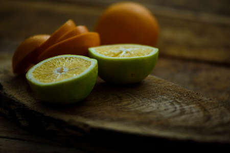 Citrus fruits are kept on a wooden plank. They are placed in such a way that they appeal the eyes of the viewers. The half cut sweet lime is mouth watering and the image feels so real.