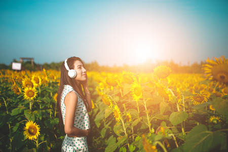 beautiful girl listening to music in field of sunflowers in the morning.