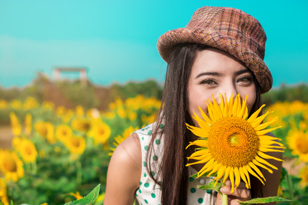 Beautiful girl holding sunflower an smiling.