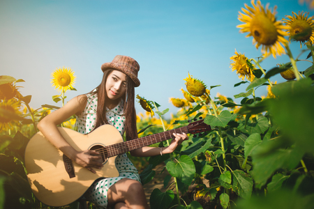 Beautiful girl playing to guitar in field of sunflowers in the morning.